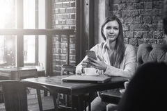单色图象 少妇坐在咖啡馆和用途智能手机的桌上 在桌上是咖啡和闭合的笔记本 库存照片
