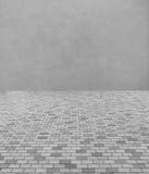 单调灰色砖石头街道路透视图  有抽象灰色墙壁的边路 免版税库存照片