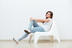单身妇女坐白色椅子 图库摄影