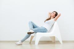 单身妇女坐白色椅子 免版税库存照片