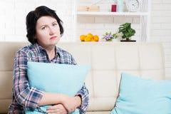 单身美女哀伤和孤独在坐沙发和拥抱枕头的卧室 免版税库存照片