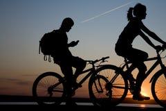 单车手夫妇日落 免版税库存图片