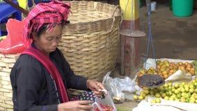 单部落女性供营商在传统服装,缅甸- 2017年11月17日的地方市场上 股票录像