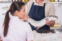 卖一条桃红色三文鱼的人 库存照片