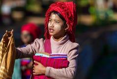 卖丝绸布料的Intha部族妇女对游人在Inle,缅甸 库存图片