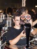 卖主倒在玻璃的啤酒给买家在街道商店在市的天的庆祝纳哈里亚在以色列 免版税库存照片