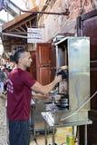 卖主切开从格栅的电shawarma在市场上的顾客的在老镇英亩在以色列 免版税库存图片