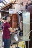 卖主切开从格栅的电shawarma在市场上的顾客的在老镇英亩在以色列 库存图片