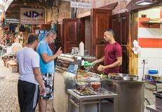卖主卖客户对在市场上的shawarma在老镇英亩在以色列 免版税库存照片