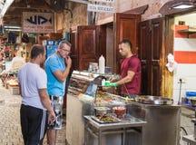 卖主卖客户对在市场上的shawarma在老镇英亩在以色列 库存图片