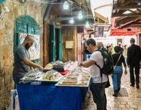 卖主卖甜点给在市场上的顾客在老镇英亩在以色列 库存图片