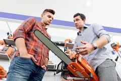 卖主在商店显示顾客一个锯 免版税库存图片