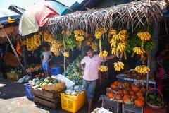 卖主在街道商店卖新鲜水果香蕉、番木瓜和菜 传统亚洲地方市场 免版税库存照片