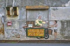 卖僳僳族大豆Asli & Segar街艺术壁画的老妇人在乔治城,槟榔岛,马来西亚 库存图片