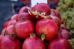 卖在地方城市市场上的堆新鲜的美丽的发光的深红石榴果子有被弄脏的背景 库存照片