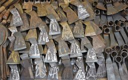 卖在地方市场上的刀子、轴和镰刀 库存照片