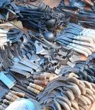 卖在地方市场上的刀子、轴和镰刀 图库摄影