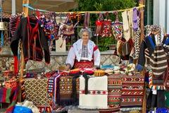 卖在摊的传统衣裳的夫人 库存图片