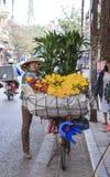 卖在河内街道上的农村妇女花在清早 免版税库存照片