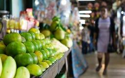 卖在泰国` s老市场上的堆绿色橙色果子与 免版税库存照片