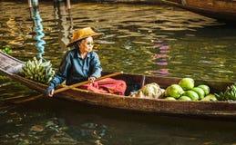 卖在浮动市场,泰国上的老妇人食物 库存照片