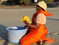 卖在海滩的美丽的橙色莎丽服的印地安妇女果子阿拉伯海 免版税库存图片