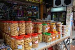 卖地方快餐的年轻人在路面的摊位在一点 库存照片