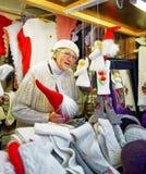 卖天使雕象的妇女在里加圣诞节市场上 图库摄影