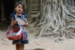 卖她的明信片的一个小女孩 免版税图库摄影