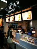 卖巧克力善良的Godiva摊位对顾客 免版税图库摄影