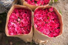 卖开花-在纸包裹的红色/桃红色玫瑰花束  库存图片