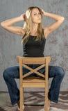 卖弄风情摆在的牛仔裤和的衬衣的年轻苗条白肤金发的女孩 库存照片