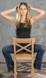 卖弄风情摆在的牛仔裤和的衬衣的年轻苗条白肤金发的女孩 免版税图库摄影