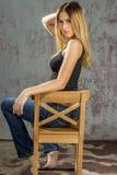 卖弄风情摆在的牛仔裤和的衬衣的年轻苗条白肤金发的女孩 图库摄影