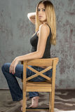 卖弄风情摆在的牛仔裤和的衬衣的年轻苗条白肤金发的女孩 库存图片