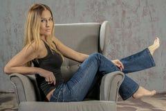 卖弄风情摆在的牛仔裤和的衬衣的年轻苗条白肤金发的女孩 免版税库存照片