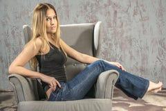 卖弄风情摆在的牛仔裤和的衬衣的年轻苗条白肤金发的女孩 免版税库存图片