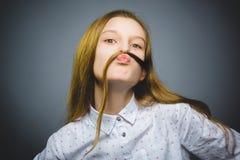 卖弄风情的女孩 在灰色隔绝的特写镜头画象英俊青少年微笑 免版税库存图片