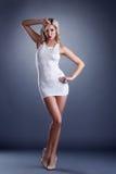 卖弄风情年轻白肤金发摆在短的礼服 库存图片