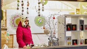 卖手工制造玩偶的妇女在圣诞节市场上在维尔纽斯 免版税库存照片