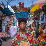卖手的一个balinesian女孩从在她的头的一个篮子扇动 免版税库存图片