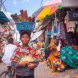 卖手的微笑的女孩从在她的头的一个篮子扇动 免版税库存图片