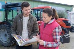 卖新的拖拉机的女推销员尝试对农夫 库存图片