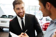 卖新的汽车的微笑的年轻经销商对一名男性顾客 库存照片