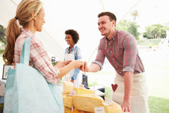 卖新鲜的干酪的人在农夫食品批发市场 免版税库存照片