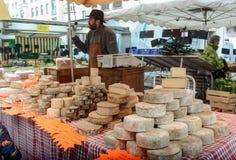 卖新鲜的干酪的人在农夫食品批发市场 图库摄影