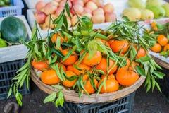 卖新鲜的普通话的亚洲农夫市场在会安市,越南 橙色和绿色 免版税图库摄影