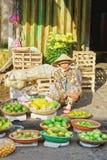 卖新鲜的香蕉芒果和石灰的亚裔贸易商 图库摄影
