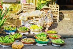 卖新鲜的香蕉芒果和石灰的亚裔贸易商 库存照片