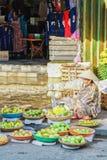 卖新鲜的香蕉芒果和石灰的亚裔贸易商 免版税库存照片